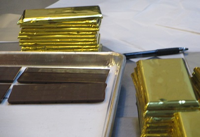 After the tempered chocolate is cooled in molds, the bars are hand wrapped in foil